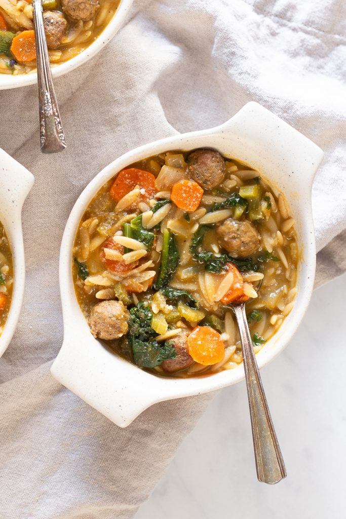 overhead photo of vegan meatballs inside white bowl of soup with a spoon sticking out.  Carrots and orzo floating around with escarole there as well.