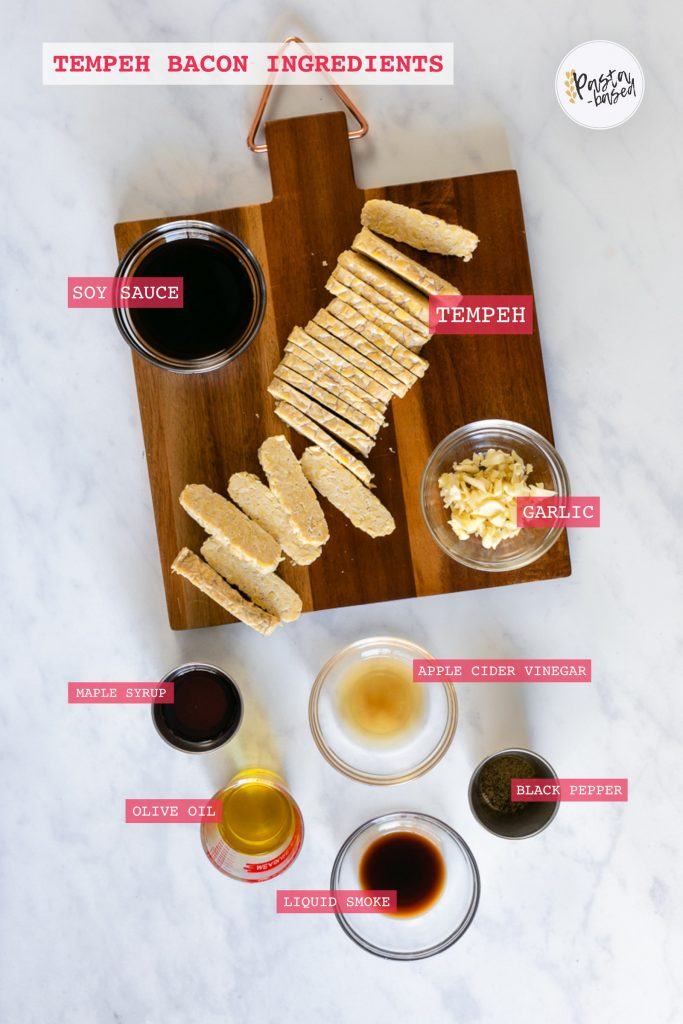 overhead graphic showing all ingredients to make this recipe.  Sliced tempeh on a brown cutting board, soy sauce, minced garlic, maple syrup, apple cider vinegar, olive oil, black pepper and liquid smoke.