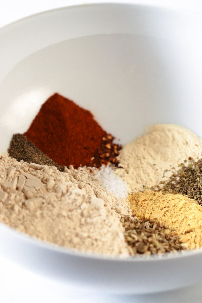 A white mixing bowl with all the dry ingredients piled up along side each other.  Vital Wheat Gluten, paprika, garlic powder, nutritional yeast, fennel, oregano, salt and pepper.